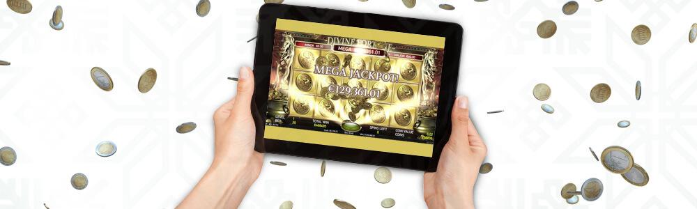 Tabletti, jossa näkyy megajackpot, ja kädet pitelemässä tablettia
