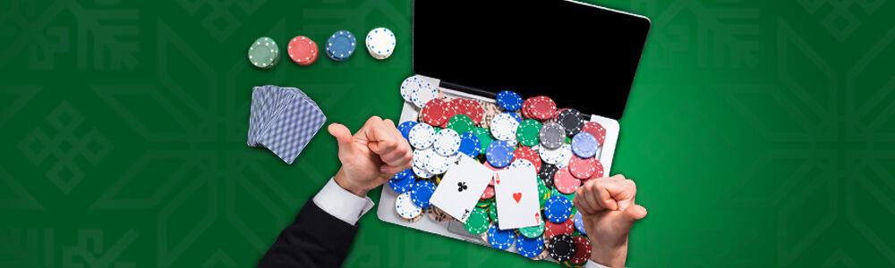 Läppäri, pelimerkkejä, pelikortteja ja kädet
