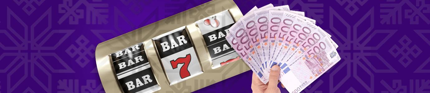 Kolikkopelin rullat ja käsi, joka pitelee nippua 500 € seteleitä