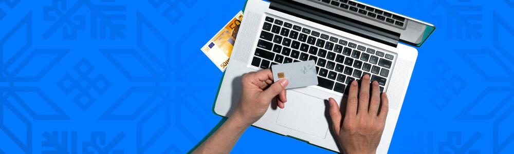 Läppäri, kädet, luottokortti ja seteli