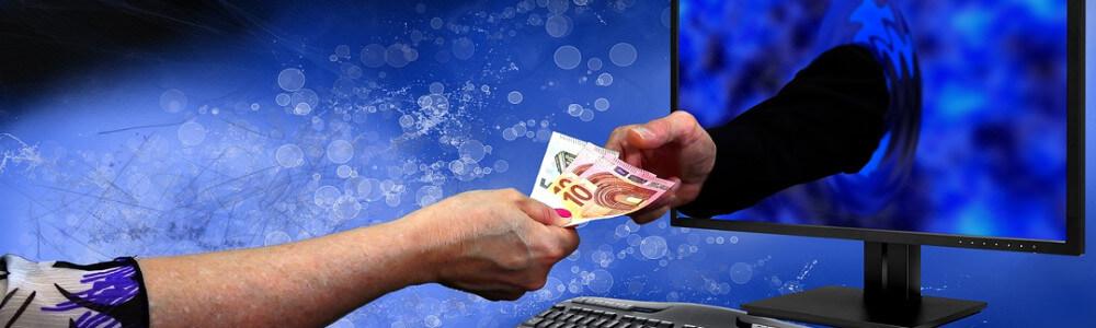 Käsi tietokoneesta antaa rahaa toiseen käteen